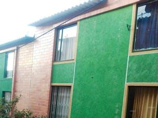 Un edificio verde con una puerta verde y un caballo marrón en VENTA CASA BOGOTA SAN VICENTE SUR