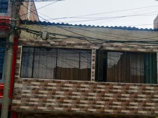 Un edificio de ladrillo rojo con una puerta roja en Casa en venta en Bosa Nova, 72m²