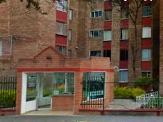 Un gran edificio de ladrillo con un banco en frente en VENTA DE APARTAMENTO BOSQUES DE KENNEDY