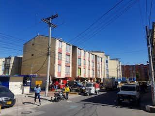 Una calle de la ciudad con coches y gente en ella en Apartamento en venta en Bosa Laureles, 52m²