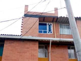 Un edificio con un reloj en el costado en VENTA CASA RENTABLE BOSA RECREO