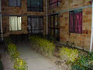 Un edificio de ladrillo con un banco en el lado en Apartamento en venta en Bosa La Paz, 47m²