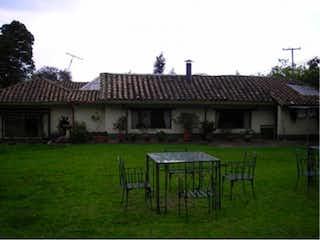 Un banco de madera sentado delante de una casa en Casa Campestre En Venta En Cota Cota