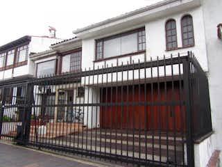 Un gran edificio de ladrillo con un banco rojo en Casa En Venta En Bogota Niza Norte
