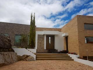 Un gran edificio de piedra con un reloj en él en Casa En Venta En Bogota Sindamanoy