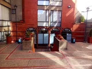 Una mujer de pie en una acera junto a un edificio en Apartamento en venta en Caobos Salazar de 3 alcoba