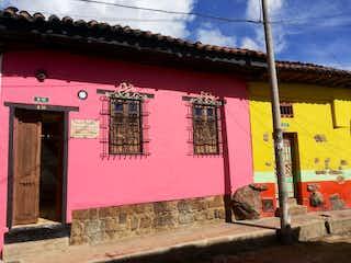 Una boca de incendios rosa frente a un edificio rosa en Casa En Venta En Bogota La Candelaria