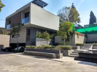 Un gran edificio de ladrillo con un banco en frente de él en Lomas Quebradas, San Jeronimo Lidice