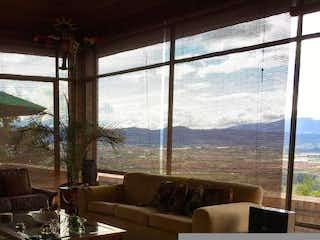 Una sala de estar llena de muebles y una gran ventana en Casa Condominio En Venta En Chia Parcelacion Sindamanoy