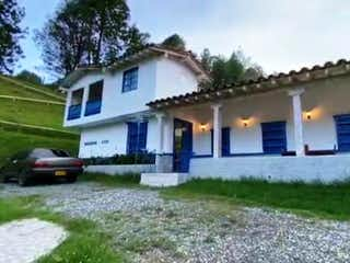 Una casa con un reloj en el costado en Finca En Venta En El Carmen De Viboral Campo Alegre