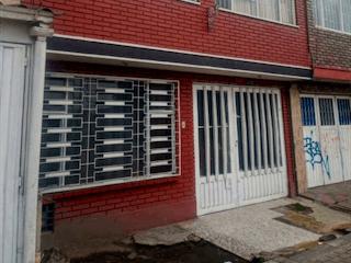 Un edificio de ladrillo rojo con una puerta roja en Venta Casa Av Abastos Carrera 80 Bomberos Kennedy