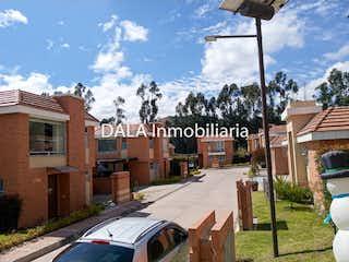 Una calle de la ciudad con un edificio y una señal de calle en SE VENDE CASA CAMPESTRE EN CAJICA CUNDINAMARCA .