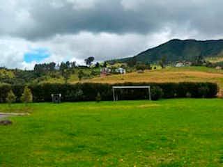 Un campo verde con una montaña en el fondo en Finca En Venta En La Calera Vereda San Jose Del Triunfo