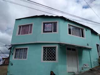 Un edificio verde con un reloj verde y blanco en Casa En Venta En Bogota Santa Cecilia Norte Parte Alta-Usaquén