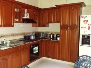 Una cocina con armarios de madera y electrodomésticos blancos en Casa en venta en Estadio de 240m²