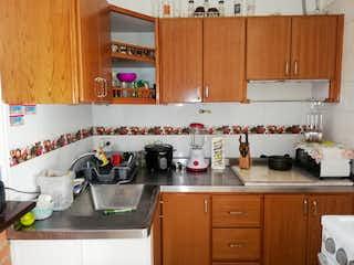 Una cocina con armarios de madera y un horno de cocina en Apartamento en venta en Lorena de 3 habitaciones
