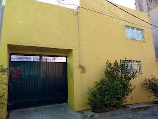 Un edificio con una puerta amarilla y una ventana en casa de 3 recamaras 3a. Cerrada de Maiz Xalpa