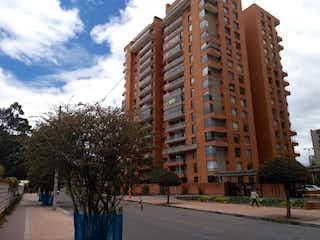 Un edificio alto sentado al lado de un árbol en Apartamento en venta en Barrio Colina Campestre de 3 alcobas