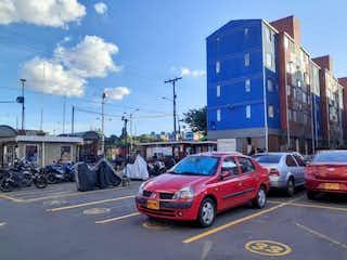 Un coche rojo está conduciendo por la calle. en VENTA DE APARTAMENTO EN TECHO KENNEDY CENTRAL