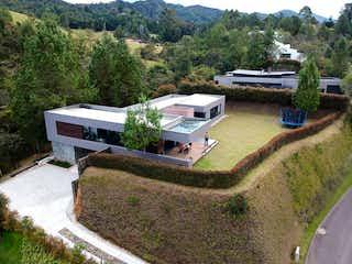 Una vista de un parque con un banco y una casa en VENTA CASA EN LA LOMA DEL ESCOBERO