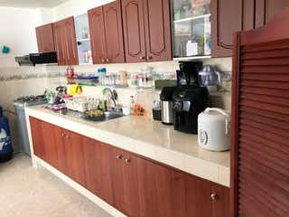 Una cocina con una estufa de fregadero y una botella de vino en Apartamento en venta en Velódromo de 4 alcobas