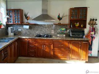 Una cocina con una estufa de fregadero y armarios en Monte Carmelo