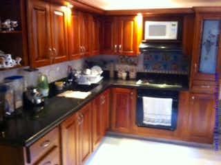 Una cocina con armarios de madera y electrodomésticos negros en CASA ALIADAS SABANETA COD 72967