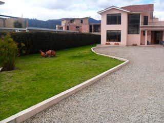 Un perro tirado en la hierba delante de una casa en Casa Campestre En Venta En Cajica Cajica