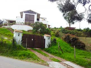 Una casa que tiene un montón de hierba y árboles en el fondo en Casa