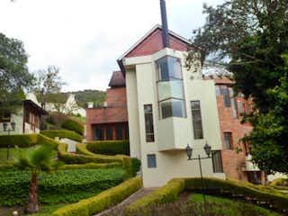 Una casa con una torre de reloj en medio de ella en Conjunto Sindamanoy