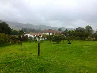Un rebaño de animales pastando en un exuberante campo verde en Finca En Venta En Suesca Finca Atma, con 5 habitaciones.