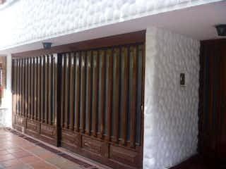 Un gato blanco y negro está mirando por una ventana en Casa En Venta En Bogota Chico, con cocina integral.