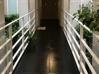 Una vista de un pasillo con un pasillo que conduce a una escalera en Apartaestudio en Bogota Chapinero - parqueadero cubierto, depósito