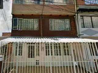 Un gran edificio con una ventana y un banco en VENTA/PERMUTA CASA RENTABLE CARVAJAL  1MAYO HOSPITAL KENNEDY