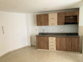 Una cocina con armarios de madera y electrodomésticos blancos en ED BRISAS DEL SUR