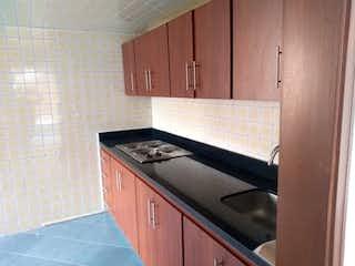 Una cocina con armarios de madera y una estufa negra en Apartamento en venta en Barrio Chapinero de 2 alcobas