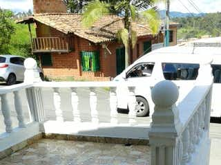 Un coche blanco estacionado junto a una boca de incendios blanca en  Venta  Vereda Alto de la Mosca, Rionegro