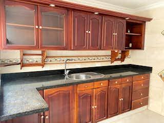 Una cocina con armarios de madera y armarios de madera en Casa en venta en Simón Bolívar de 4 alcobas