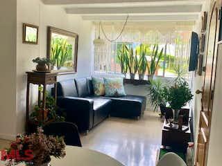 Una sala de estar llena de muebles y flores en Tierra Del Sol (Esmeraldal)