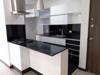 Una cocina con armarios blancos y electrodomésticos negros en Apartamento para la venta loma de Cumbres