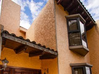 Un edificio con un reloj en el costado en Venta Linda Casa en Condominio en Tehuixtle, Valle Escondido, Tlalpan