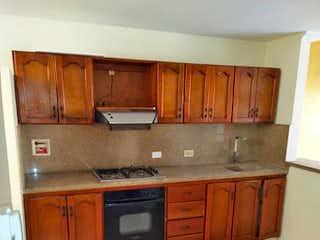 Una cocina con armarios de madera y electrodomésticos blancos en Apartamento en venta en Casco Urbano Caldas, de 120mtrs2