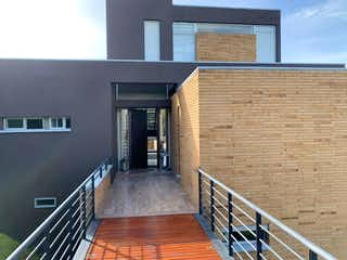 Un edificio de ladrillo con un banco en frente en Financio Espectacular Casa - Prados del Este la Calera