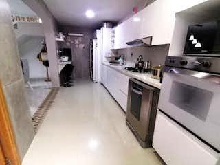 Una cocina con una estufa y un refrigerador en HERMOSO CASA EN VENTA LOS COLORES 243 METROS
