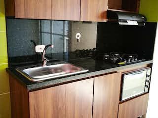 Una cocina con armarios de madera y una estufa negra en APARTAMENTO EN VENTA BELLO ESTACIN MADERA