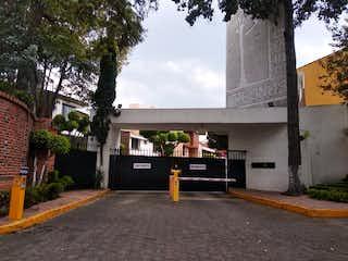 Una persona sentada en un banco frente a un edificio en Casa en VENTA, Calzada Arenal Tepepan