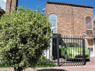 Un edificio verde con una planta verde en frente en Vendo casa de dos pisos en Chia excelente sector