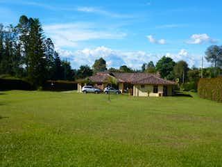 Un campo herboso con un gran edificio en el fondo en Finca Llano Grande, Casa en venta en Altos De La Pereira de 4 alcobas