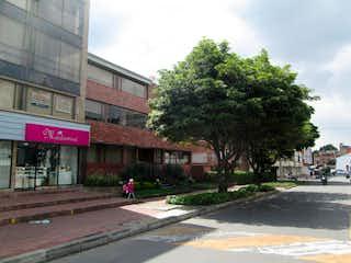 Una persona caminando por una calle cerca de un edificio en Apartamento En Venta En Bogota Santa Bárbara