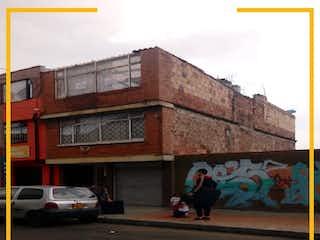 Un edificio con un reloj en el costado en SE VENDE CASA EN EL BARRIO SANTA SOFIA.